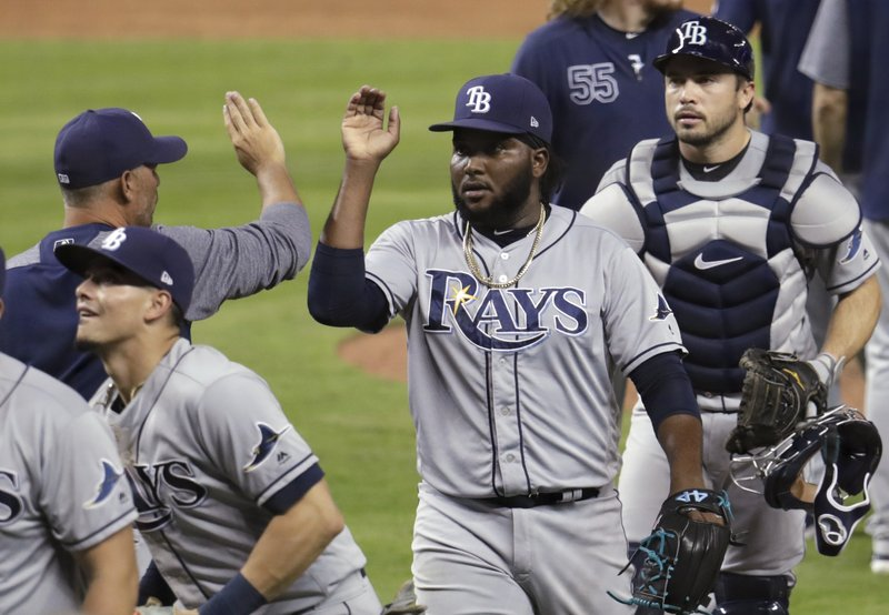 Tampa Bay Rays manager Kevin Cash, left, high-fives relief pitcher Diego Castillo, center, after the Rays defeated the Miami Marlins 1-0 in a baseball game Wednesday, May 15, 2019, in Miami. At right is Rays catcher Travis d'Arnaud. (AP Photo/Lynne Sladky)