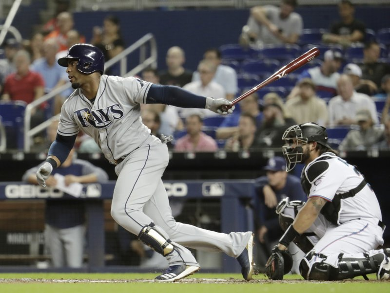 Tampa Bay Rays' Yandy Diaz watches his single during the fifth inning as Miami Marlins catcher Jorge Alfaro watches during a baseball game Wednesday, May 15, 2019, in Miami. (AP Photo/Lynne Sladky)