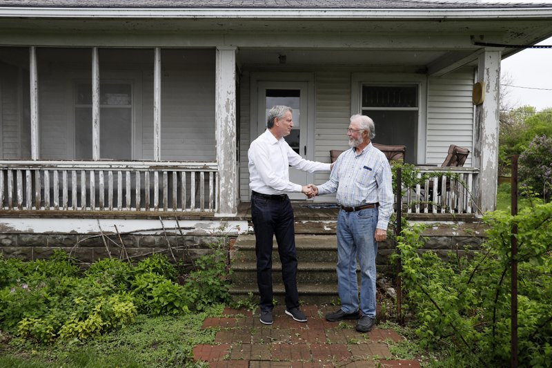 Democratic presidential candidate New York Mayor Bill de Blasio talks with George Naylor, right, after a meeting with Greene County small family farmers, Friday, May 17, 2019, in Churdan, Iowa. (AP Photo/Charlie Neibergall)