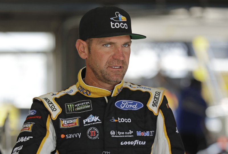 Clint Bowyer waits by his car before practice for Saturday's NASCAR All-Star Cup series auto race at Charlotte Motor Speedway in Concord, N.C., Friday, May 17, 2019. (AP Photo/Chuck Burton)