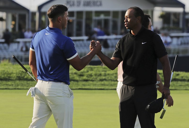 Brooks Koepka, left, shakes hands with Tiger Woods after finishing the second round of the PGA Championship golf tournament, Friday, May 17, 2019, at Bethpage Black in Farmingdale, N.Y. (AP Photo/Charles Krupa)