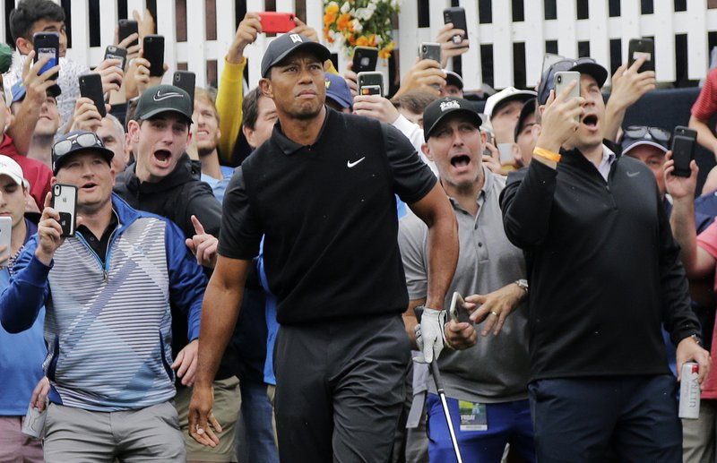 Tiger Woods watches his shot out of the rough on the first hole during the second round of the PGA Championship golf tournament, Friday, May 17, 2019, at Bethpage Black in Farmingdale, N.Y. (AP Photo/Seth Wenig)