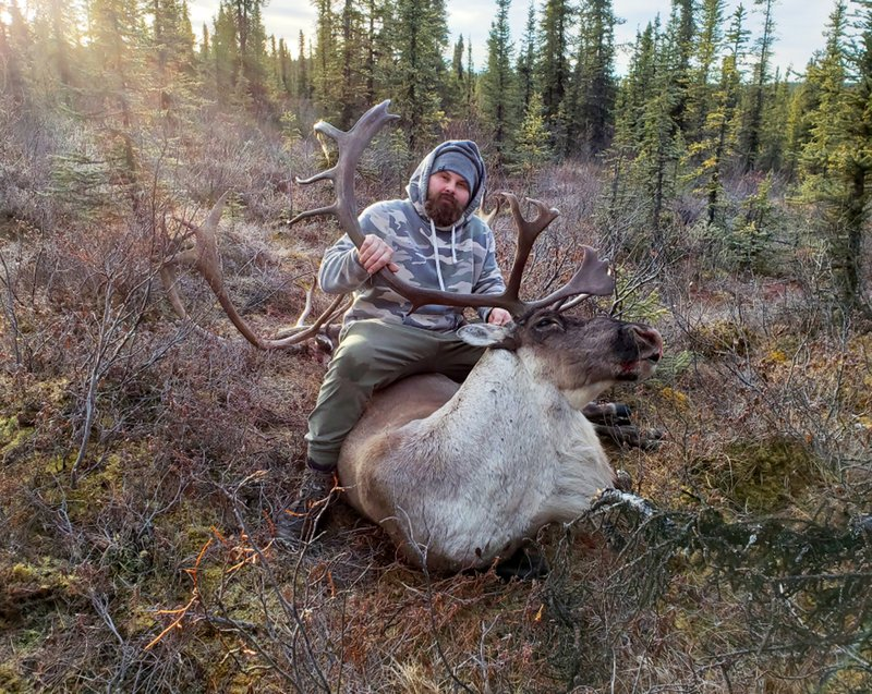This 2018 photo provided by Aleksandr Neverov shows him with a caribou during a hunt near Glennallen, Alaska. Neverov was hunting with his friend, Viacheslav Akimenko, earlier this month in Kodiak, Alaska. Akimenko left the men's hunting camp, and Neverov found his friend's body six days later, about a mile from camp with no apparent signs the man was mauled by a bear or harmed himself. (Aleksandr Neverov via AP)