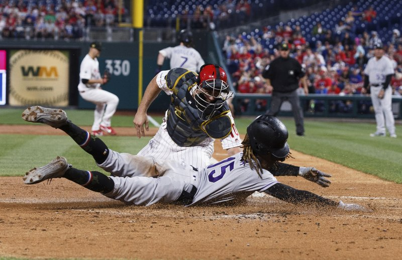 Colorado Rockies' Raimel Tapia, right, scores a run on a grounder by Brendan Rodgers (7) as Philadelphia Phillies catcher J.T. Realmuto, left, was late with the tag during the second inning of a baseball game Friday, May 17, 2019, in Philadelphia. (AP Photo/Chris Szagola)