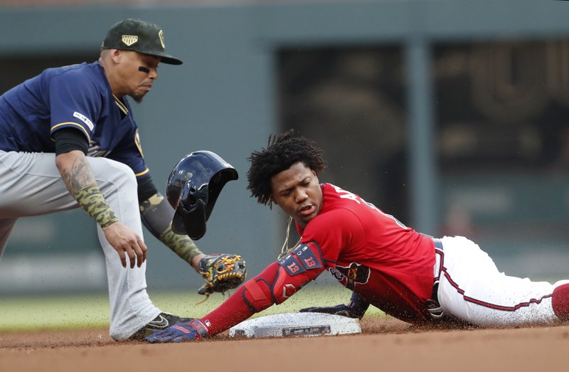 Atlanta Braves left fielder Ronald Acuna Jr. (13) is safe at second base with a double as Milwaukee Brewers shortstop Orlando Arcia (3) handles the late throw during the first inning of a baseball game Friday, May 17, 2019, in Atlanta. (AP Photo/John Bazemore)