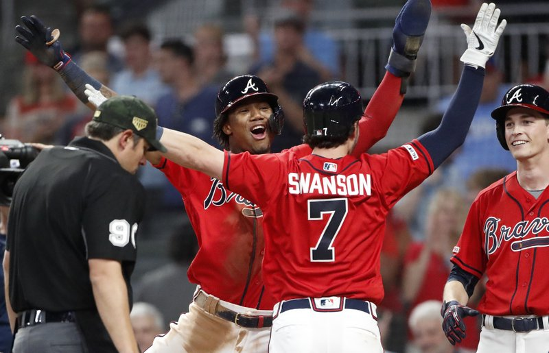 Atlanta Braves' Dansby Swanson (7) celebrates with Ronald Acuna Jr. after hitting a three-run home run in the sixth inning of the team's baseball game against the Milwaukee Brewers on Friday, May 17, 2019, in Atlanta. (AP Photo/John Bazemore)