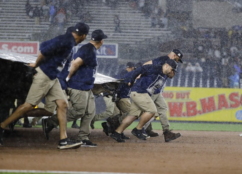 Members of the grounds crew cover the field during a rain delay in the eighth inning of a baseball game between the New York Yankees and the Tampa Bay Rays at Yankee Stadium on Friday, May 17, 2019, in New York. (AP Photo/Frank Franklin II)