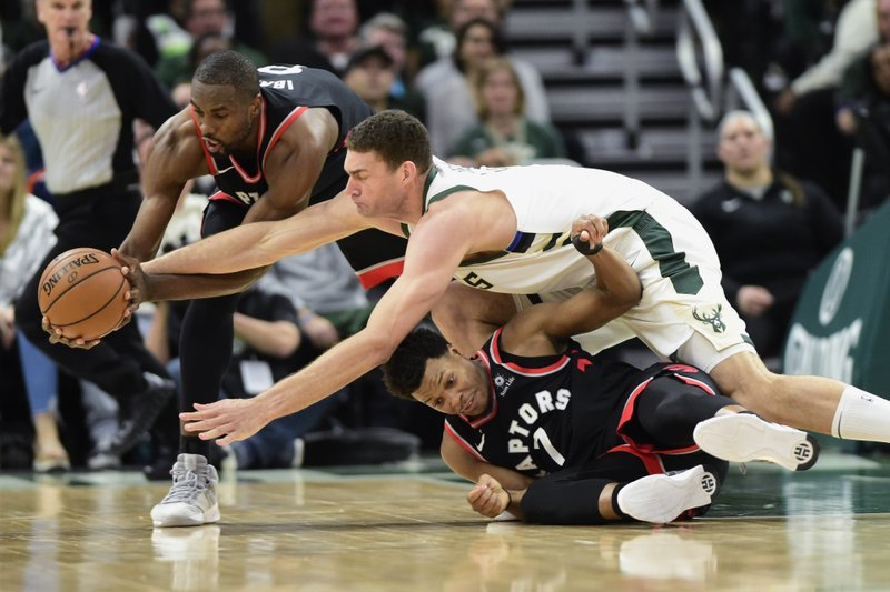 Milwaukee Bucks centrerBrook Lopez battles Toronto Raptors guard Kyle Lowry (7) and center Serge Ibaka (9) for the ball and picks up a foul on the play during the second half of Game 2 of the NBA basketball playoffs Eastern Conference finals, Friday, May 17, 2019, in Milwaukee. (Frank Gunn/The Canadian Press via AP)