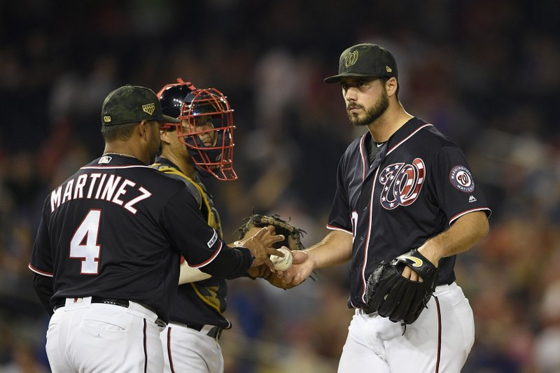 Washington Nationals relief pitcher Kyle Barraclough, right, is pulled from a baseball game by manager Dave Martinez (4) during the eighth inning against the Chicago Cubs, Friday, May 17, 2019, in Washington. Nationals catcher Kurt Suzuki, back center, looks on. (AP Photo/Nick Wass)