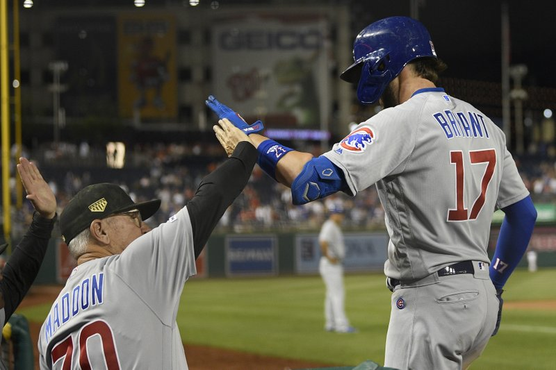Chicago Cubs' Kris Bryant (17) celebrates his two-run home run with manager Joe Maddon (70) during the ninth inning of a baseball game against the Washington Nationals, Friday, May 17, 2019, in Washington. (AP Photo/Nick Wass)