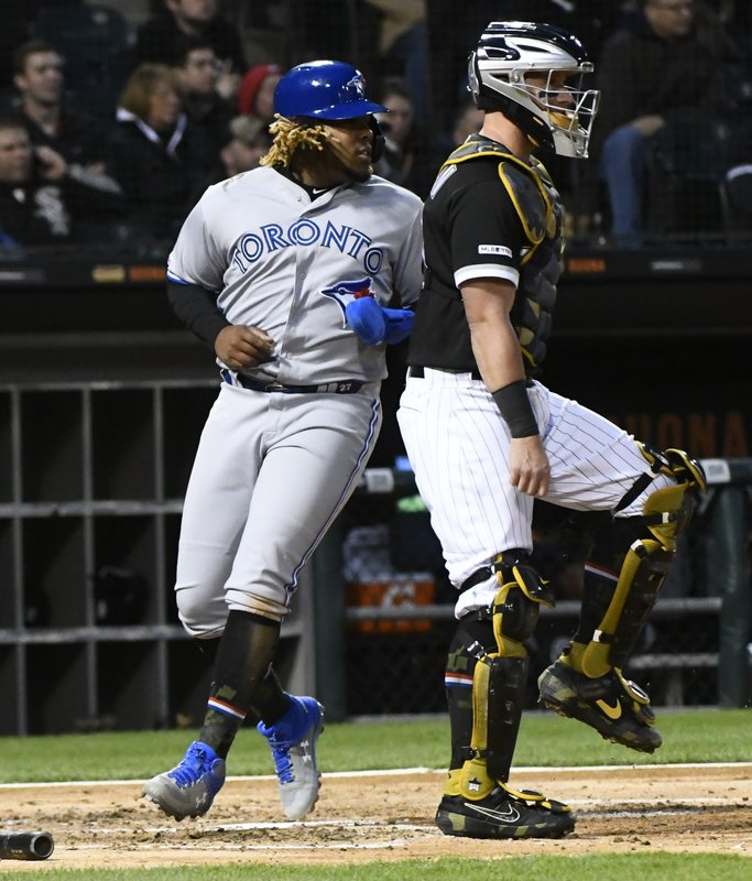 Toronto Blue Jays' Vladimir Guerrero Jr., left, scores past Chicago White Sox catcher James McCann during the third inning of a baseball game Friday, May 17, 2019, in Chicago. (AP Photo/Matt Marton)