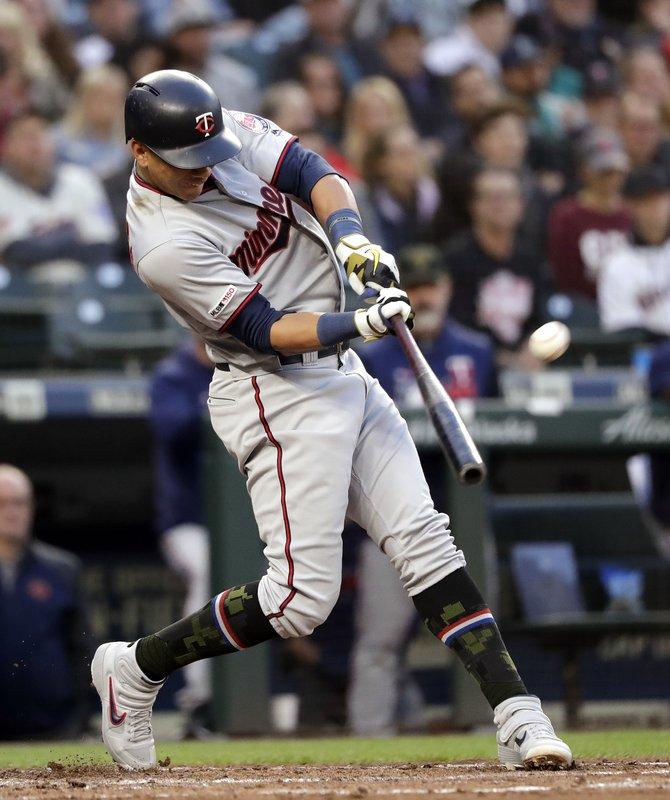 Minnesota Twins' Ehire Adrianza hits an RBI sacrifice fly against the Seattle Mariners during the fourth inning of a baseball game Friday, May 17, 2019, in Seattle. (AP Photo/Elaine Thompson)
