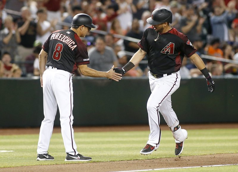 Arizona Diamondbacks' David Peralta, right, is congratulated by third base coach Tony Perezchica after hitting a solo home run against the San Francisco Giants during the fourth inning of a baseball game, Friday, May 17, 2019, in Phoenix. (AP Photo/Ralph Freso)