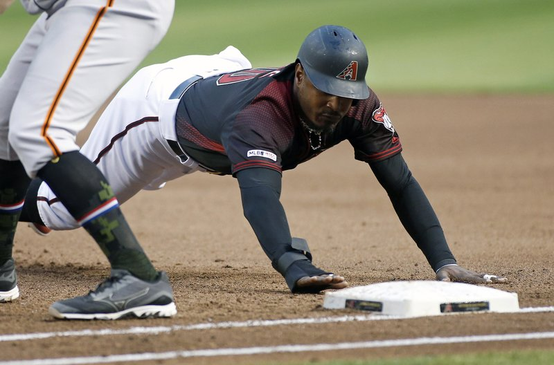 Arizona Diamondbacks' Adam Jones dives back to first base on a pickoff-attempt by the San Francisco Giants during the second inning of a baseball game, Friday, May 17, 2019, in Phoenix. (AP Photo/Ralph Freso)