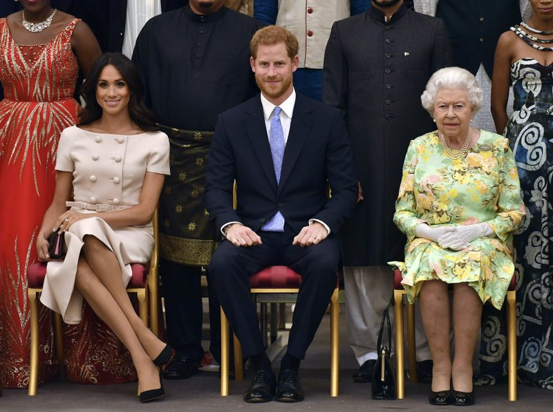 FILE - In this Tuesday, June 26, 2018 file photo, Britain's Queen Elizabeth, Prince Harry and Meghan, Duchess of Sussex pose for a group photo at the Queen's Young Leaders Awards Ceremony at Buckingham Palace in London. Sunday, May 19, 2019 marks the first wedding anniversary of the besotted couple.  (John Stillwell/Pool Photo via AP, File)