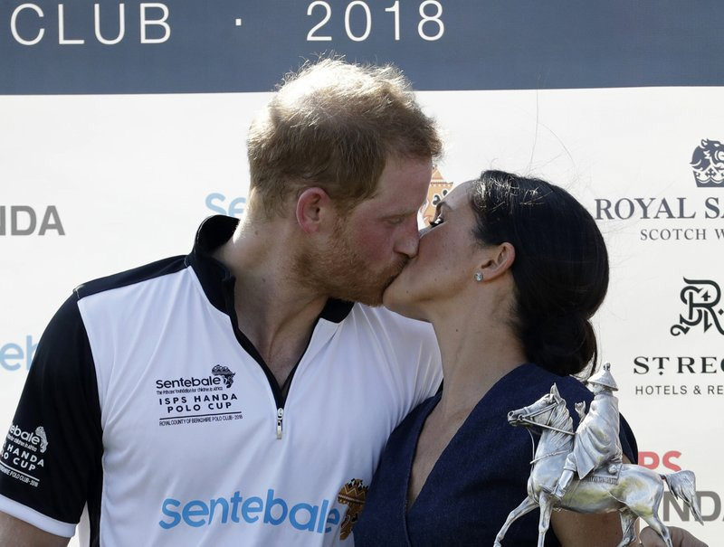 FILE - In this Thursday, July 26, 2018 file photo, Meghan, Duchess of Sussex and Britain's Prince Harry kiss during the presentation ceremony for the Sentebale ISPS Handa Polo Cup at the Royal County of Berkshire Polo Club in Windsor, England. Sunday, May 19, 2019 marks the first wedding anniversary of the besotted couple. (AP Photo/Matt Dunham, File)