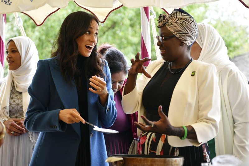 FILE - In this Thursday, Sept. 20, 2018 file photo, Meghan, the Duchess of Sussex, left, reacts with one of the women behind the cookbook