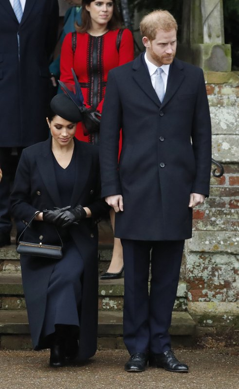 FILE - In this Tuesday, Dec. 25, 2018 file photo, Britain's Prince Harry, stands as Meghan, Duchess of Sussex curtsies to Britain's Queen Elizabeth II as she leaves in a car after attending the Christmas day service at St Mary Magdalene Church in Sandringham in Norfolk, England. Sunday, May 19, 2019 marks the first wedding anniversary of the besotted couple.  (AP Photo/Frank Augstein, File)