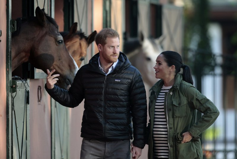 FILE - In this Monday, Feb. 25, 2019 file photo, Britain's Prince Harry and Meghan, Duchess of Sussex, walk together during a visit to the Moroccan Royal Equestrian Sports Complex in Rabat, Morocco. (AP Photo/Mosa'ab Elshamy, File)