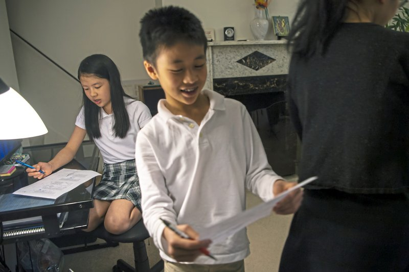 Vivian Loh, a seventh grader at Winchester Thurston School and the first girl to win the Pennsylvania MATHCOUNTS competition, explains the solution to a math problem to her brother Vincent, 10, after they both completed a practice worksheet in the morning before school, Thursday, April 25, 2019, at their home in Squirrel Hill. (Alexandra Wimley/Pittsburgh Post-Gazette via AP)