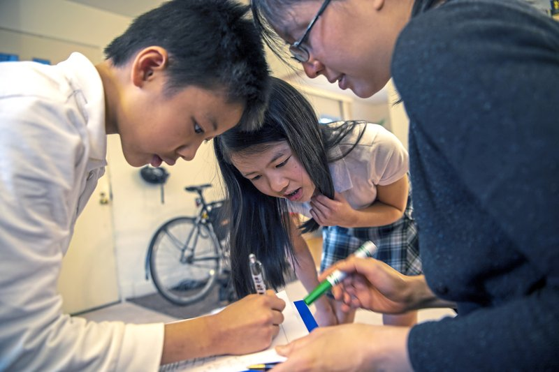 Vivian Loh, center, a seventh grader at Winchester Thurston School and the first girl to win the Pennsylvania MATHCOUNTS competition, explains the solution to a math problem to her brother Vincent, 10, and their mother Debbie after they each completed a practice worksheet in the morning before school, Thursday, April 25, 2019, at their home in Squirrel Hill. (Alexandra Wimley/Pittsburgh Post-Gazette via AP)