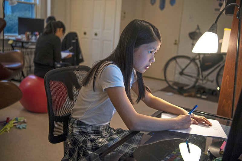 Vivian Loh, a seventh grader at Winchester Thurston School and the first girl to win the Pennsylvania MATHCOUNTS competition, works on a math practice worksheet in the morning before school, Thursday, April 25, 2019, at her home in Squirrel Hill, Pa. (Alexandra Wimley/Pittsburgh Post-Gazette via AP)
