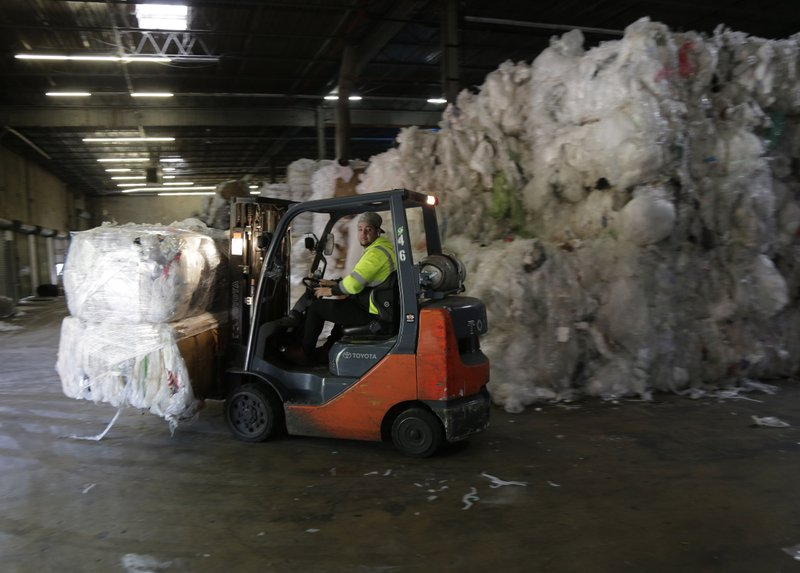 In this May 7, 2019 photo, a forklift moves through stacks of recyclables at a GDB International warehouse in Monmouth Junction, N.J. GDB International exported bales of scrap plastic film such as pallet wrap and grocery bags for years. But when China started restricting imports, company president Sunil Bagaria installed new machinery to process it into pellets he sells profitably to manufacturers of garbage bags and plastic pipe. (AP Photo/Seth Wenig)