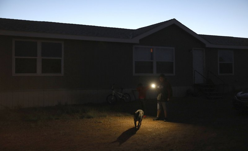 In this Wednesday, May 8, 2019 photo, Jimmy Long Jr. uses his cell phone flashlight to find his way to get something from his truck outside his Kaibeto home on the Navajo Reservation. Long has lived with his family in a home that had no electricity for more than a decade. An ambitious project to connect homes to the electric grid on the country's largest American Indian reservation is wrapping up. Utility crews from across the U.S. have volunteered their time over the past few weeks to hook up about 300 homes on the Navajo Nation. (AP Photo/Jake Bacon)
