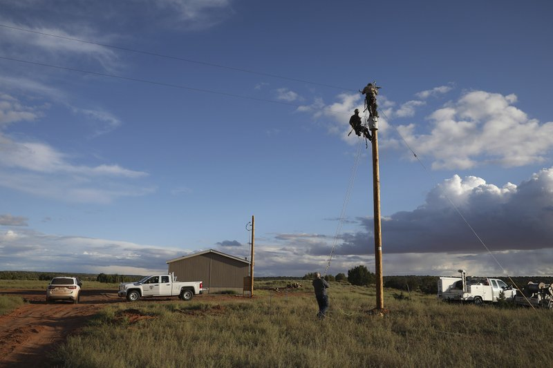 In this Wednesday, May 8, 2019 photo, utility workers prepare a power pole to connect a home in Kaibeto on the Navajo Nation to the electric grid. Miranda Haskie and her husband Jimmie Long Jr. have lived in the home with their son Jayden Long, 13, for more than a decade without electricity. An ambitious project to connect homes to the electric grid on the country's largest American Indian reservation is wrapping up. Utility crews from across the U.S. have volunteered their time over the past few weeks to hook up about 300 homes on the Navajo Nation. (AP Photo/Jake Bacon)