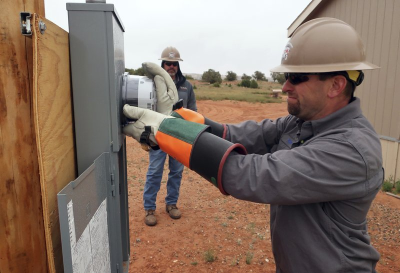 In this Thursday, May 9, 2019 photo Ken Wagner, a journeyman lineman with Piqua Power System in Piqua, Ohio, installs an electric meter at a home in Kaibeto, Arizona, on the Navajo Nation, as his co-worker, Kevin Grinstead, looks on. An ambitious project to connect homes to the electric grid on the country's largest American Indian reservation is wrapping up. Utility crews from across the U.S. have volunteered their time over the past few weeks to hook up about 300 homes on the Navajo Nation. (AP Photo/Felicia Fonseca)