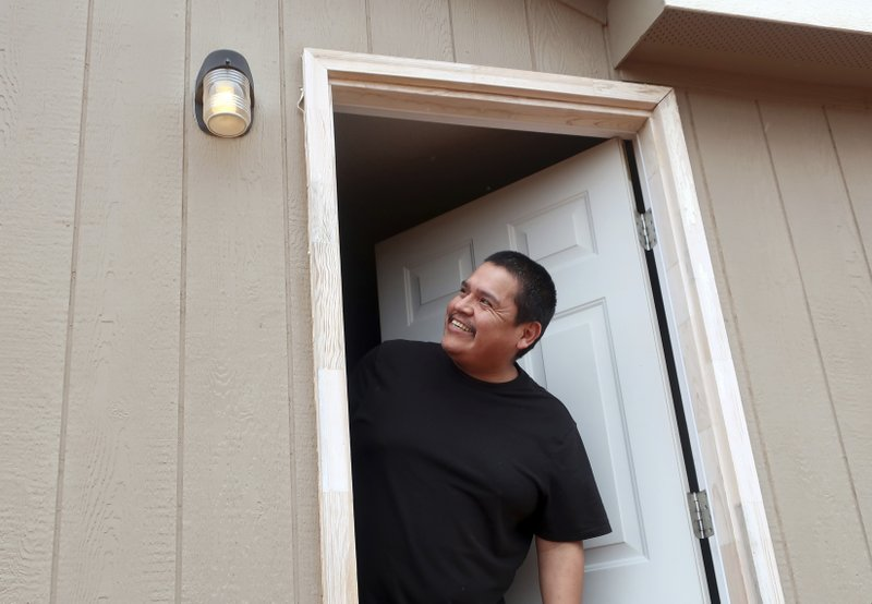 In this Thursday, May 9, 2019 photo Jimmie Long Jr. smiles after a utility crew hooks up power to his home in Kaibeto, Arizona, on the Navajo Nation. An ambitious project to connect homes to the electric grid on the country's largest American Indian reservation is wrapping up. Utility crews from across the U.S. have volunteered their time over the past few weeks to hook up about 300 homes on the Navajo Nation. (AP Photo/Felicia Fonseca)