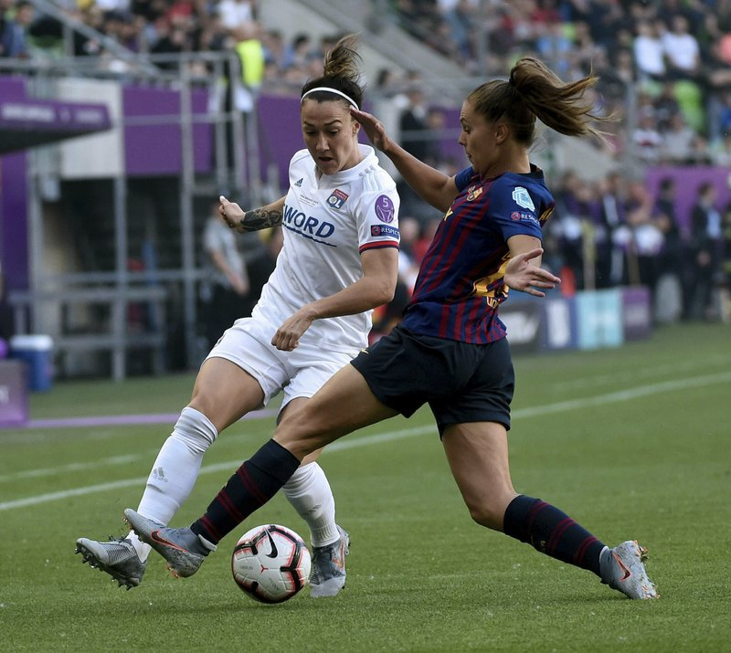 Lucy Bronze of Lyon, left, in action against Lieke Martens of Barcelona during the women's soccer UEFA Champions League final match between Olympique Lyon and FC Barcelona at the Groupama Arena in Budapest, Hungary, Saturday, May 18, 2019. (Tibor Illyes/MTI via AP)