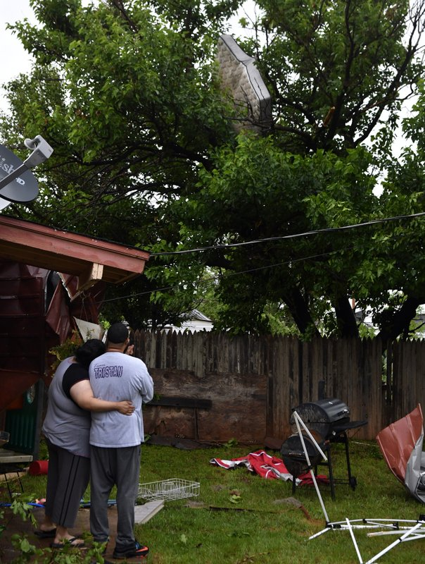 Amanda Crisp rests her head on the shoulder of her husband, Julius, as they look up at a mattress hanging in a tree over their home in Abilene, Texas, on Saturday, May 18, 2019. Many residents said a tornado struck in the early morning hours. (Ronald W. Erdrich/The Abilene Reporter-News via AP)