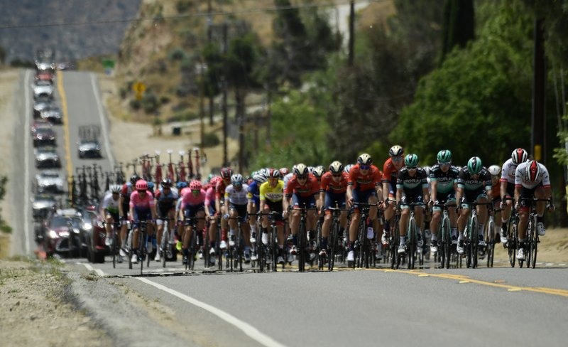 The peloton rides a long straightaway during the seventh and final stage of the Tour of California bicycle race Saturday, May 18, 2019, near Santa Clarita, Calif. (AP Photo/Mark J. Terrill)