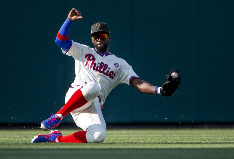 Philadelphia Phillies center fielder Andrew McCutchen (22) fields a single by Colorado Rockies' Trevor Story during the fifth inning of a baseball game, Saturday, May 18, 2019, in Philadelphia. (AP Photo/Laurence Kesterson)