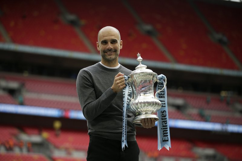 Manchester City's manager Pep Guardiola poses for a picture as lifts the trophy after winning the English FA Cup Final soccer match between Manchester City and Watford at Wembley stadium in London, Saturday, May 18, 2019. Manchester City won 6-0. (AP Photo/Tim Ireland)