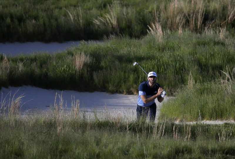 Dustin Johnson watches his shot out of a bunker on the 18th hole during the third round of the PGA Championship golf tournament, Saturday, May 18, 2019, at Bethpage Black in Farmingdale, N.Y. (AP Photo/Seth Wenig)