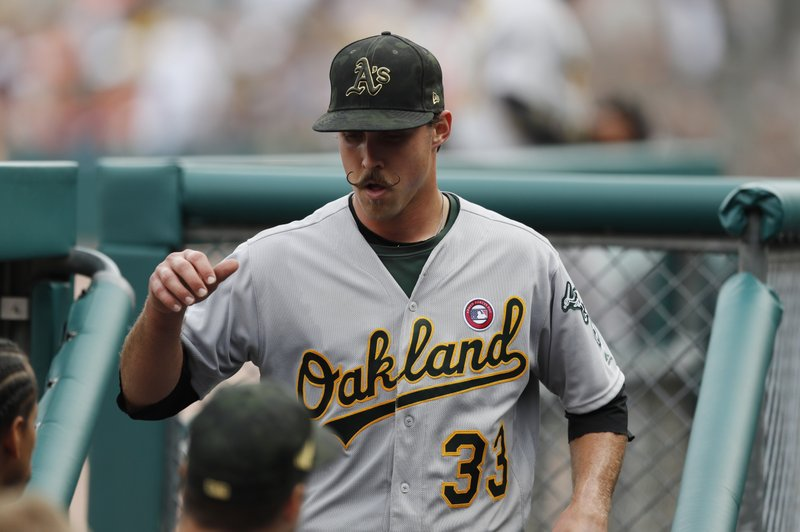 Oakland Athletics starting pitcher Daniel Mengden is greeted in the dugout after the seventh inning of the team's baseball game against the Detroit Tigers, Saturday, May 18, 2019, in Detroit. Mengden pitched seven innings to lift the Athletics to their 15th straight win over Detroit, 4-1. (AP Photo/Carlos Osorio)