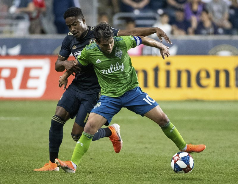 Seattle Sounders' Nicolas Lodeiro, right, keeps the ball from Philadelphia Union's Sergio Santos during the first half of an MLS soccer match Saturday, May 18, 2019, in Chester, Pa. (AP Photo/Chris Szagola)