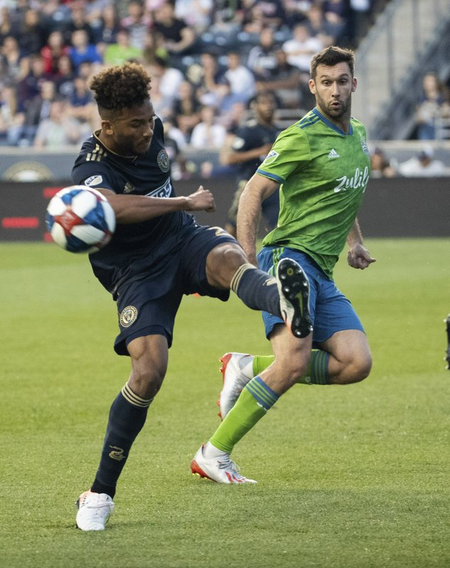 Philadelphia Union's Auston Trusty, left, kicks the ball away from Seattle Sounders' Will Bruin during the first half of an MLS soccer match Saturday, May 18, 2019, in Chester, Pa. (AP Photo/Chris Szagola)