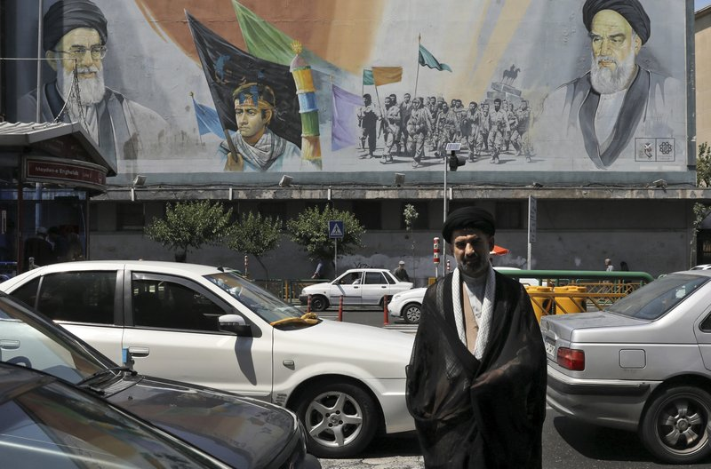In this Friday, May 17, 2019 photo, a cleric crosses Enqelab-e-Eslami (Islamic Revolution) street in front of a mural depicting late Iranian revolutionary founder Ayatollah Khomeini, right, Supreme Leader Ayatollah Ali Khamenei, left, and the Basij paramilitary force, in downtown Tehran, Iran. (AP Photo/Vahid Salemi)