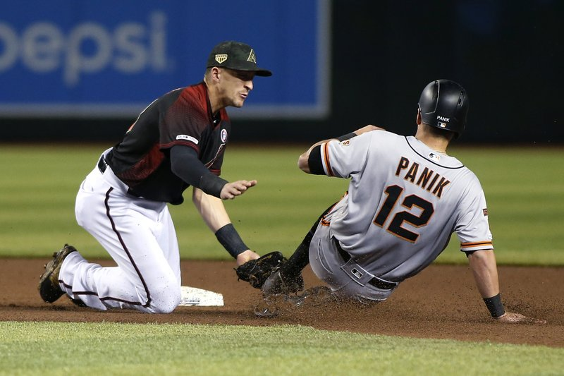 Arizona Diamondbacks shortstop Nick Ahmed, left, tags out San Francisco Giants' Joe Panik on a steal attempt during the fourth inning of a baseball game Saturday, May 18, 2019, in Phoenix. (AP Photo/Ralph Freso)