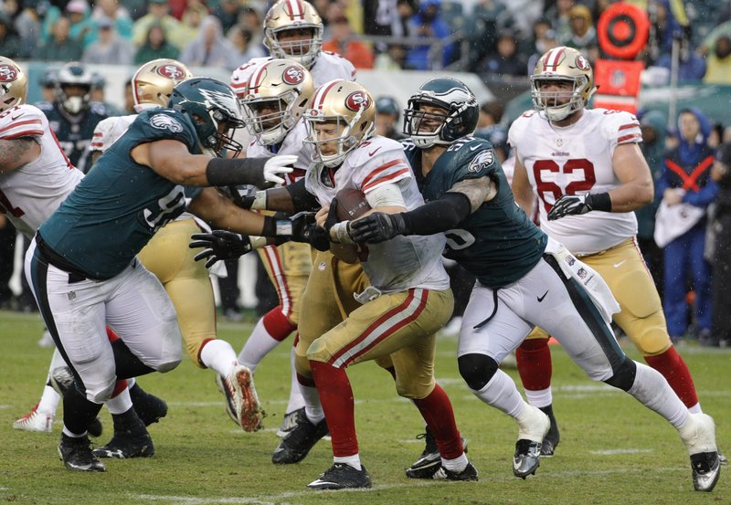 FILE - In this Oct. 29, 2017, file photo, Philadelphia Eagles' Destiny Vaeao (97) and Chris Long (56) take down San Francisco 49ers' C.J. Beathard during the second half of an NFL football game in Philadelphia. Long has announced his retirement from football, ending an 11-year NFL playing career that included winning two Super Bowl titles and the Walter Payton Man of the Year Award. Long posted his decision Saturday night, May 18, on Twitter, saying it has