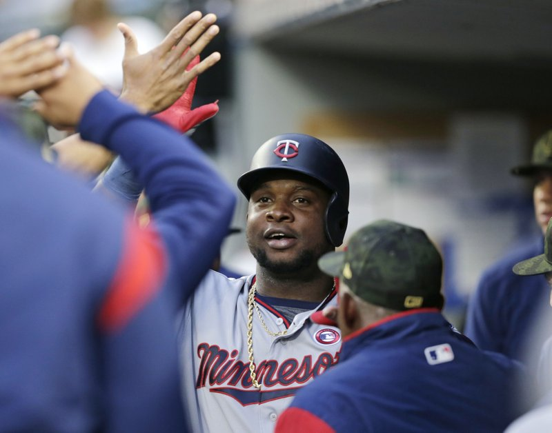 Minnesota Twins' Miguel Sano is congratulated in the dugout after hitting a solo home run against the Seattle Mariners during the third inning of a baseball game Saturday, May 18, 2019, in Seattle. (AP Photo/John Froschauer)