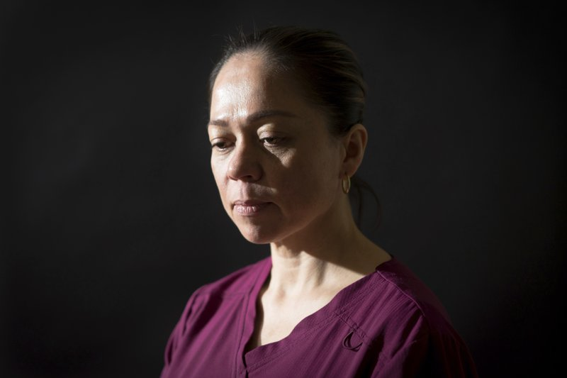 In this Friday, March 4, 2019 photo, Julie Riduta poses for a photograph in the home where she works as a caretaker in Berkeley, Calif. At a previous job, Riduta suffered a miscarriage after lifting a heavy patient into bed. Residential senior care homes are treating workers as indentured servants – and profiting handsomely. The profit margins can be huge and, for violators of labor laws, hinge on the widespread exploitation of thousands of caretakers, many of them poor immigrants effectively earning $2 to $3.50 an hour to work around the clock. (James Tensuan/Reveal via AP)