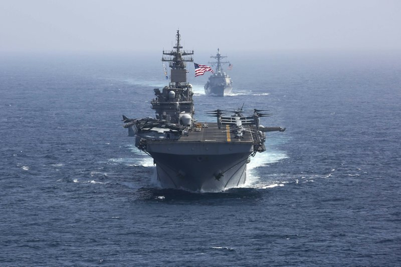 CORRECTS DATE - In this Friday, May 17, 2019, photo released by the U.S. Navy, the amphibious assault ship USS Kearsarge and the Arleigh Burke-class guided-missile destroyer USS Bainbridge sail in formation as part of the USS Abraham Lincoln aircraft carrier strike group in the Arabian Sea. Commercial airliners flying over the Persian Gulf risk being targeted by