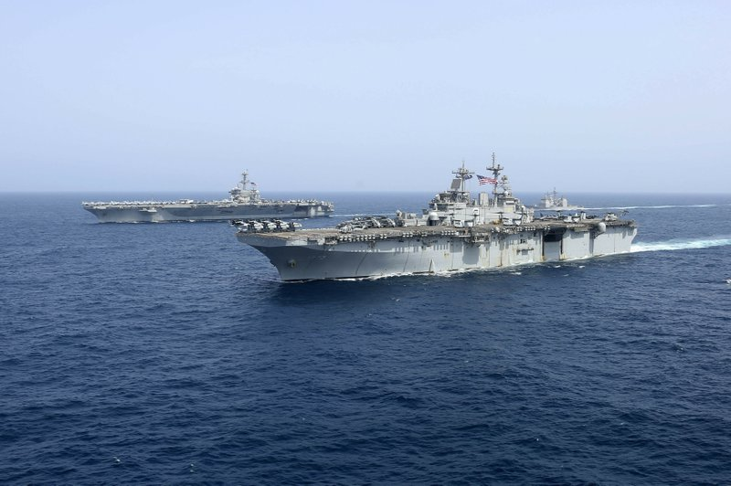 CORRECTS DATE - In this Friday, May 17, 2019, photo released by the U.S. Navy, the amphibious assault ship USS Kearsarge sails in front of the USS Abraham Lincoln aircraft carrier in the Arabian Sea. Commercial airliners flying over the Persian Gulf risk being targeted by