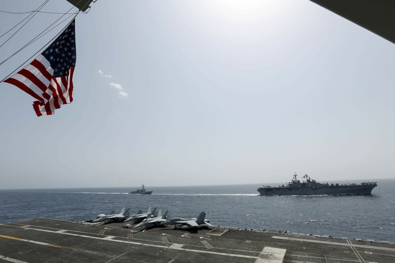 CORRECTS DATE - In this Friday, May 17, 2019, photo, released by the U.S. Navy, the amphibious assault ship USS Kearsarge, right, and the Arleigh Burke-class guided-missile destroyer USS Bainbridge, left, are seen from the Nimitz-class aircraft carrier USS Abraham Lincoln as they sail in the Arabian Sea. Commercial airliners flying over the Persian Gulf risk being targeted by