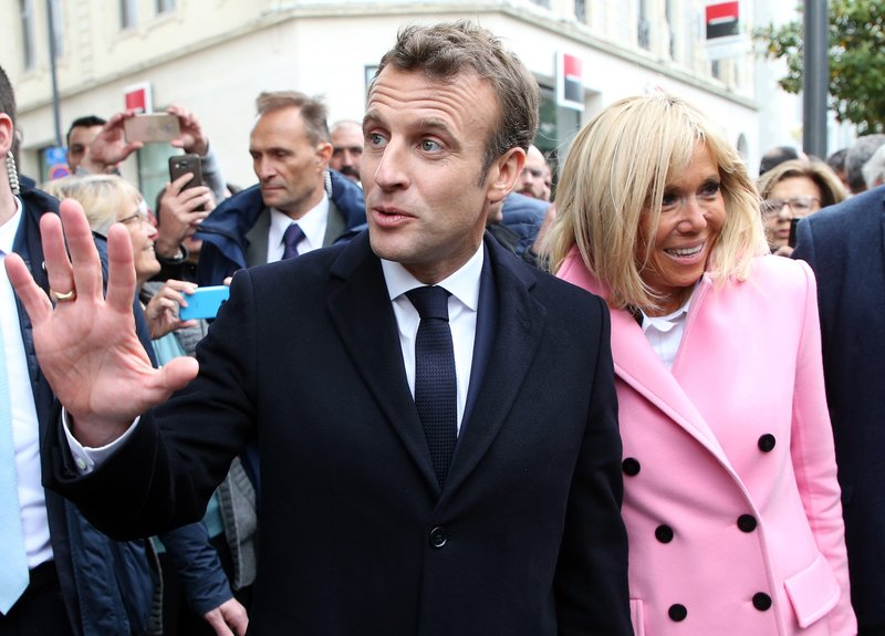 France's President Emmanuel Macron gestures as he walks with his wife Brigitte during a visit to Biarritz, southwestern France, Friday, May 17, 2019. (AP Photo/Bob Edme)