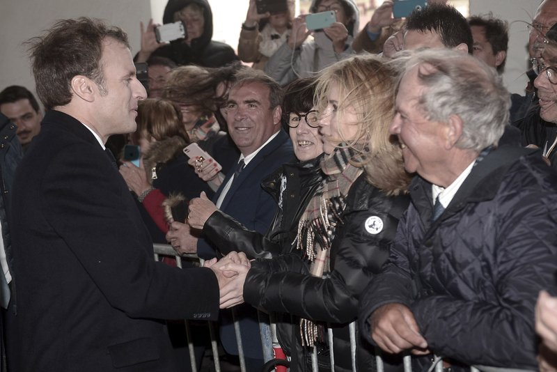 French President Emmanuel Macron, left, shakes hands with residents as he arrives to prepare the upcoming G7 in Biarritz, southwestern France, Friday May 17, 2019. The G7 Summit will take place in Biarritz on Aug. 25-27 2019. (Iroz Gaizka/Pool via AP)